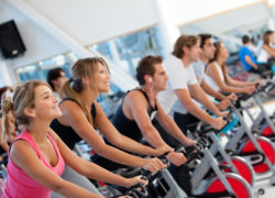 Group of gym people on spinning machines